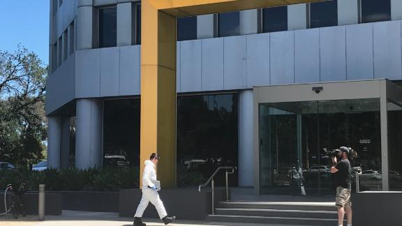 An emergency worker in a hazardous material suit enters the South Korean consulate in Melbourne.
