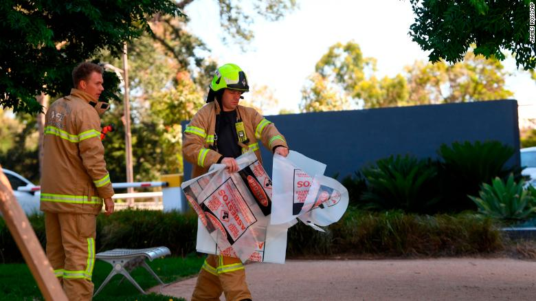 A firefighter is seen carrying a hazardous material bag into the South Korean consulate in Melbourne.