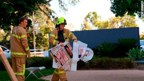 A firefighter carries a hazardous material bag into the Korean Consulate in Melbourne on Wednesday.