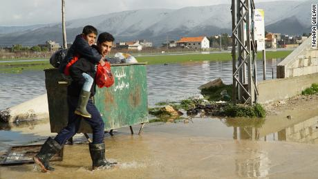 A teenager carries a boy across a flooded street near a Syrian refugee camp.