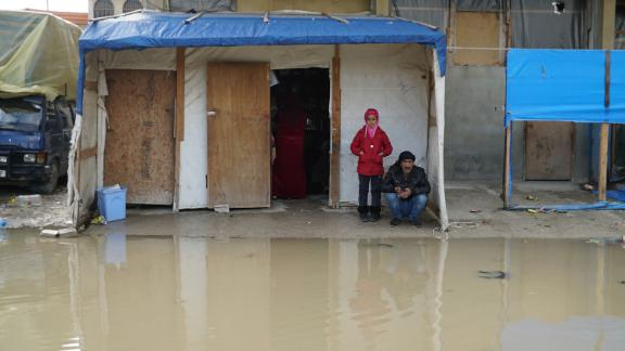 A girl and her father, Syrian refugees, have been living in a corner shop for nearly three years. They woke up on Tuesday to find that they were surrounded by water.