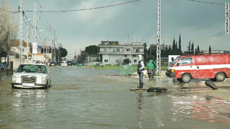 Cars on the road near the refugee camps in the Bar Elias area drive through half a meter of water.