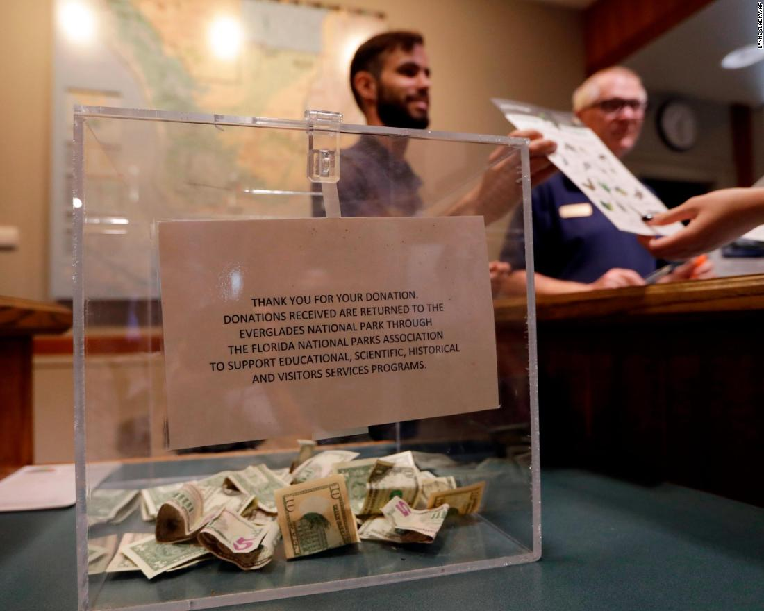 A donation box sits on the counter at the Ernest F. Coe Visitor Center in Florida's Everglades National Park. Dany Garcia, center, was being paid by the Florida National Parks Association to work in the center during the partial government shutdown.