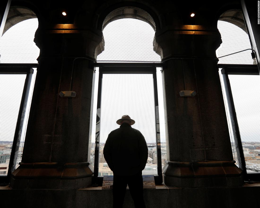 A National Park Service ranger looks out onto Washington from the Trump International Hotel's historic clock tower.