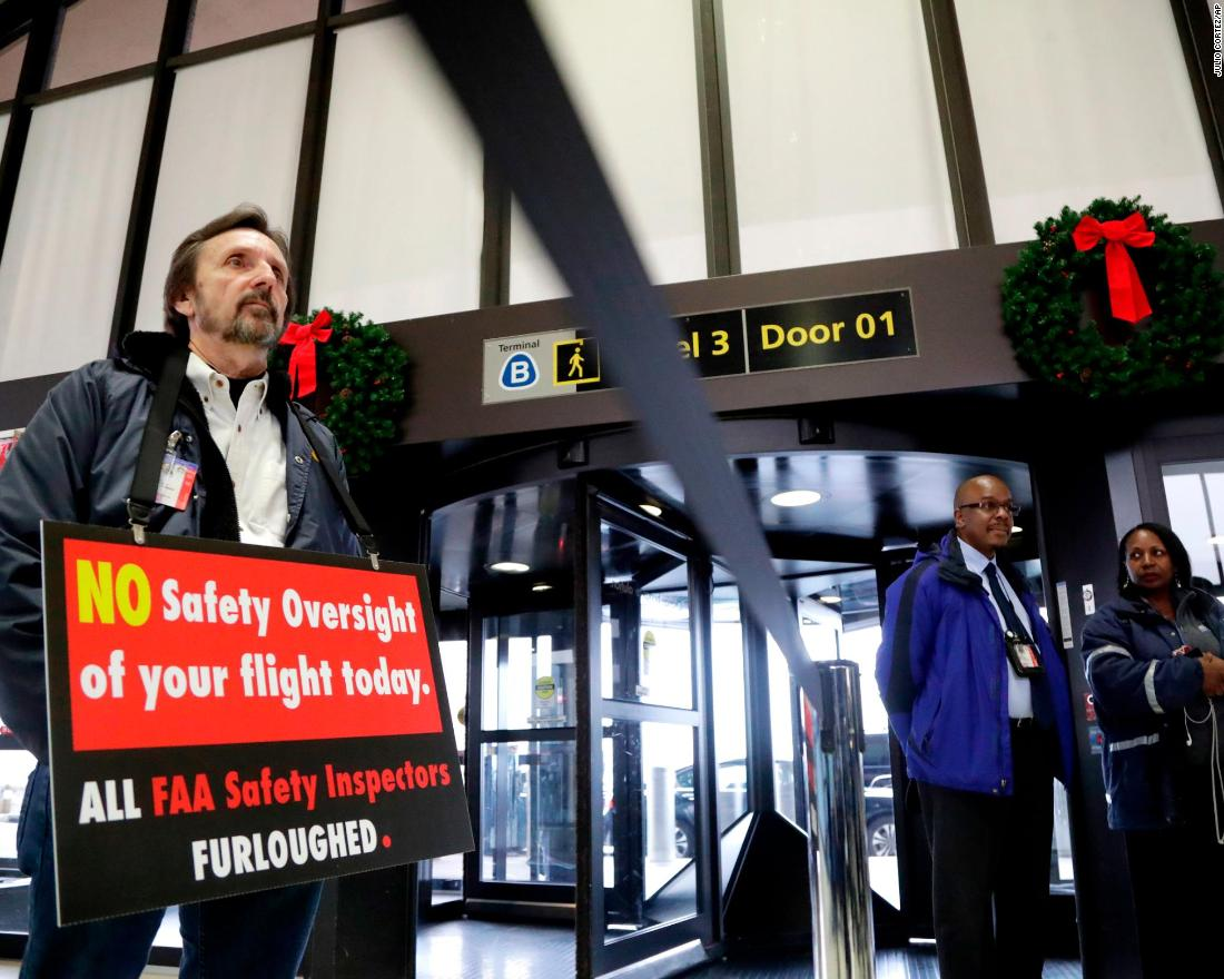 Federal Aviation Administration employee Michael Jessie, who was working without pay as an aviation safety inspector, holds a sign Tuesday, January 8, while attending a news conference at Newark Liberty International Airport in New Jersey.