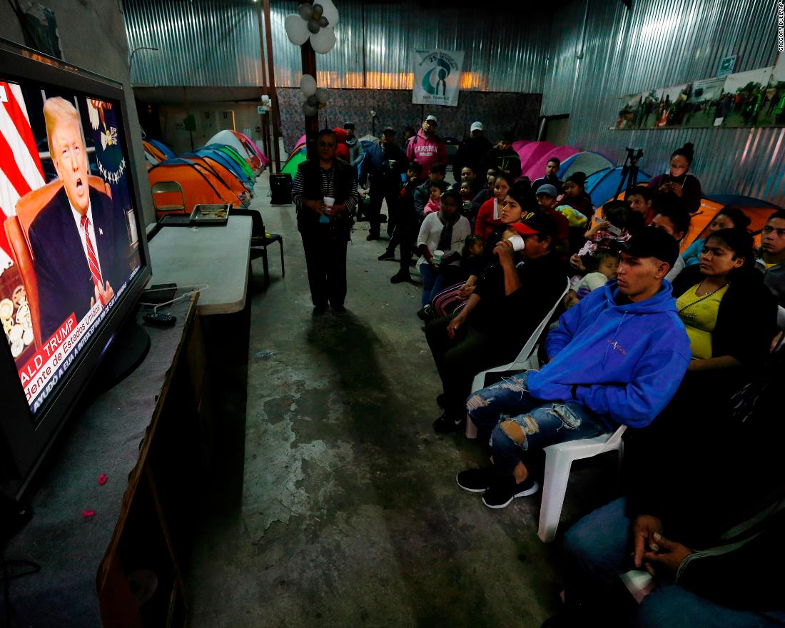 Migrants from Mexico and Central America watch Trump's speech from a shelter in Tijuana, Mexico, on January 8.