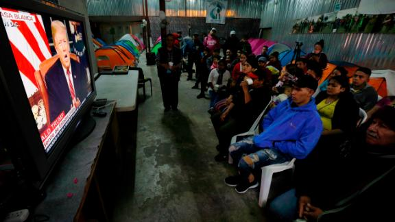 Migrants from Mexico and Central America watch Trump
