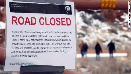 Visitors walk through the visitor center parking lot past a road which is closed because of the partial government shutdown, in Arches National Park, Utah, U.S., January 9, 2019.  REUTERS/George Frey