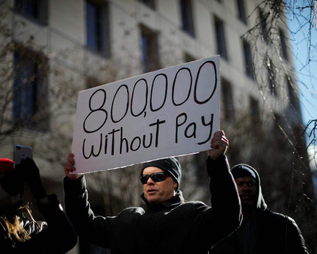 A protester holds a sign during a rally in Washington on January 10. Around 800,000 federal workers were out of work or were working without pay because of the shutdown.
