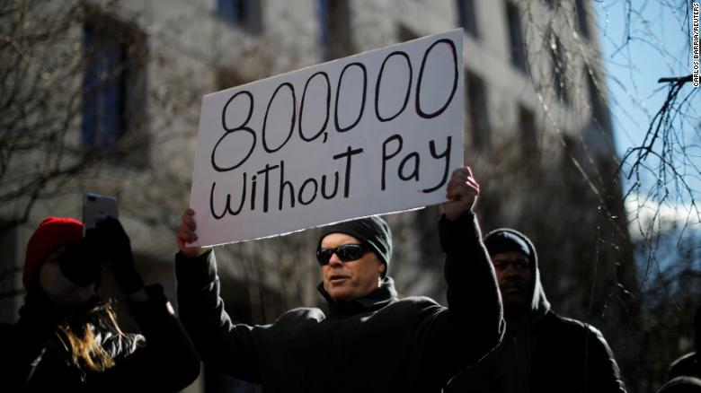 "A demonstrator holds a sign, signifying hundreds of thousands of federal employees who won't be receiving their paychecks as a result of the partial government shutdown, during a ""Rally to End the Shutdown"" in Washington."