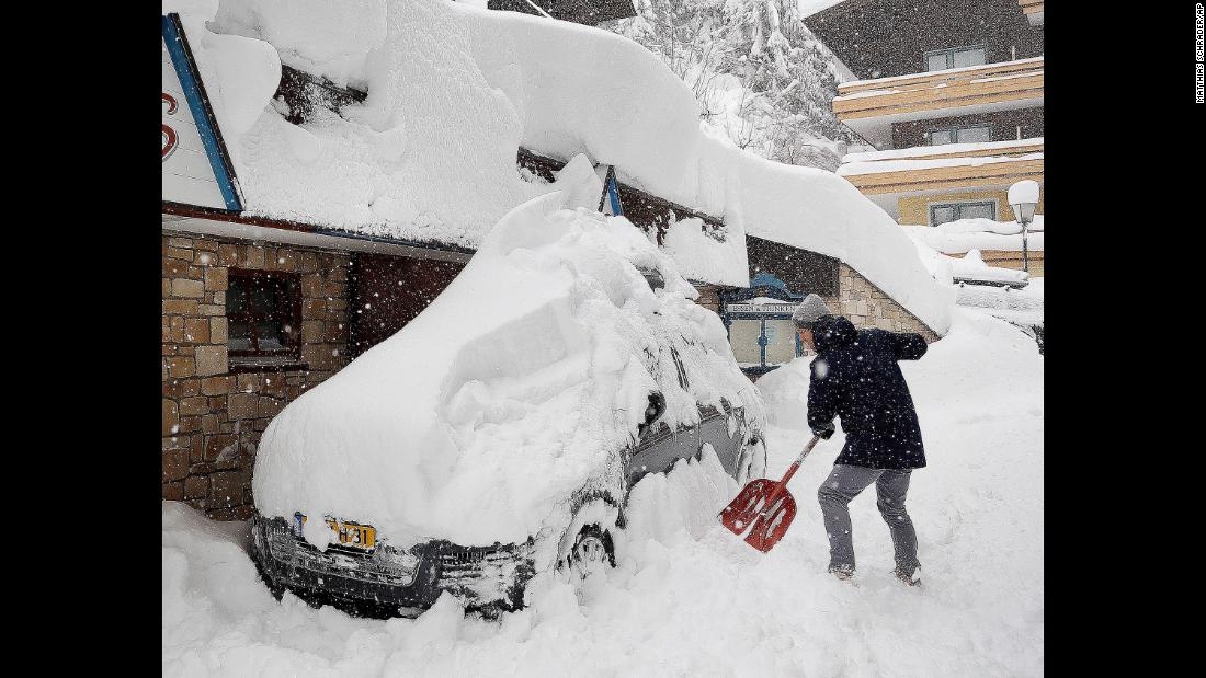 A ski tourist digs out a car after heavy snow falls in Filzmoos, Austria, on Saturday, January 5.
