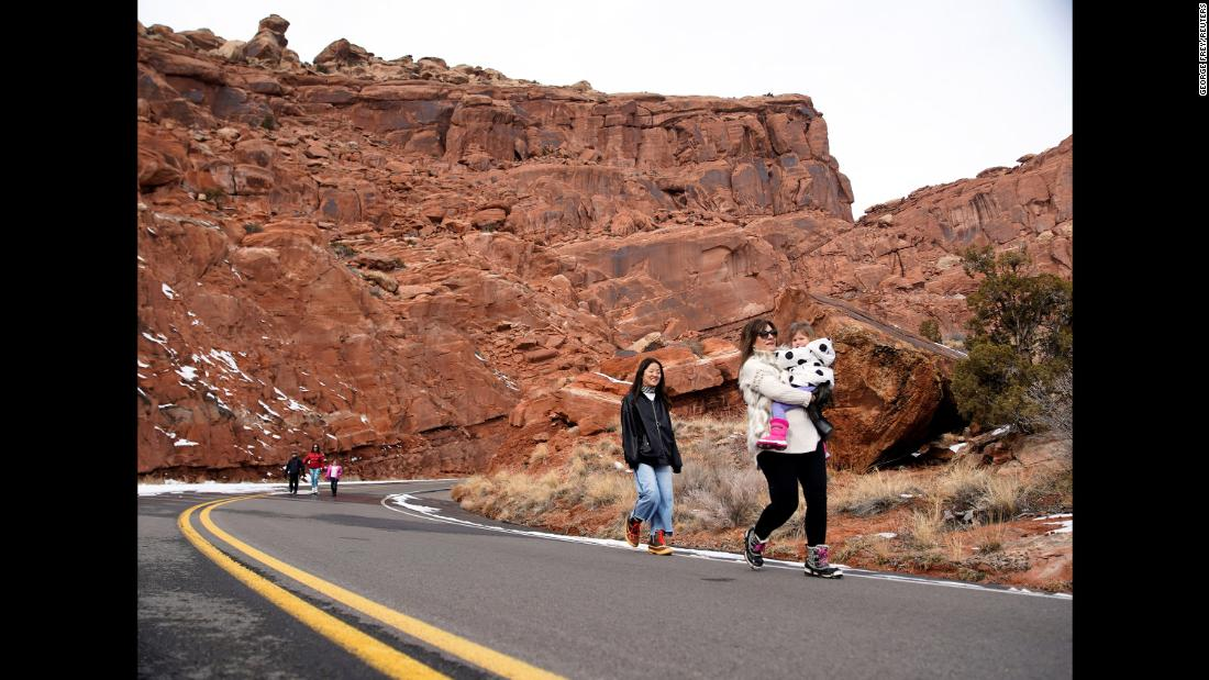 Visitors walk down the main road of Arches National Park in Utah on Wednesday, January 9. The road is closed to vehicle traffic because of the government shutdown.