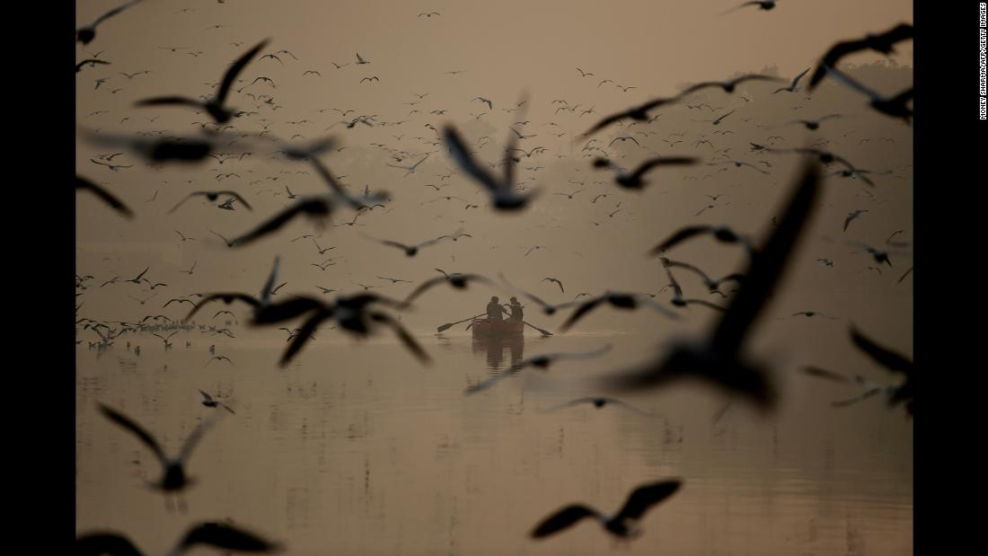 People take a ride on a boat near the banks of the Yamuna River in New Delhi on Friday, January 4.