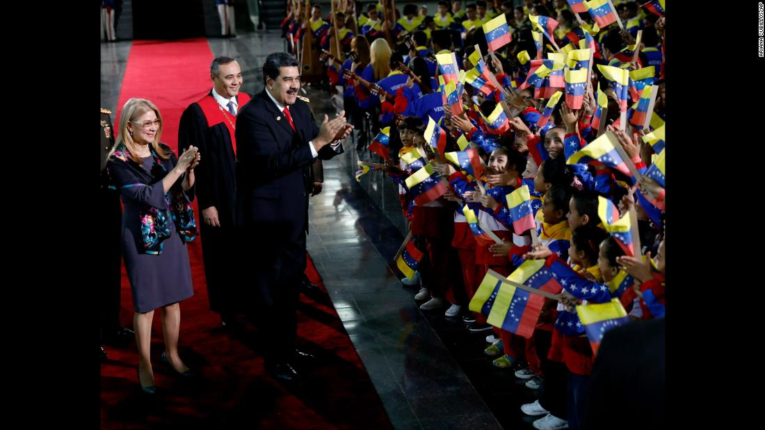 Venezuela's President Nicolas Maduro and first lady Cilia Flores stop to greet flag-waving children upon arrival at the Supreme Court for Maduro's inauguration ceremony in Caracas, Venezuela, on Thursday, January 10.