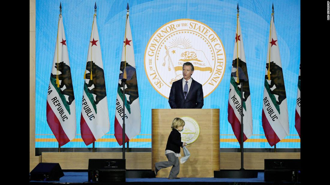 California Gov. Gavin Newsom speaks during his inauguration as his son, Dutch, runs around the podium Monday, January 7.