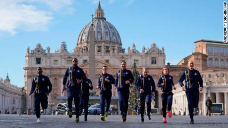 Members of the Athletica Vaticana sports team run in front of St. Peter's Basilica on Thursday.