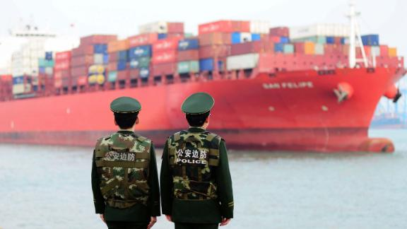 Police officers watching a cargo ship at a port in Qingdao in 2018. China's official growth rate for last year is expected to be around 6.5%, the weakest in nearly three decades.