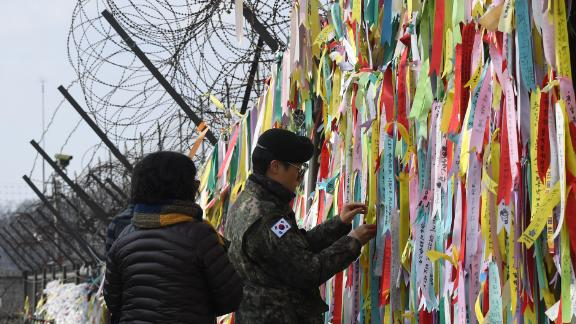 A South Korean soldier looks at ribbons with inscriptions calling for peace and reunification displayed on a military fence near the Demilitarized Zone (DMZ) dividing the two Koreas in the border city of Paju on January 1, 2019.