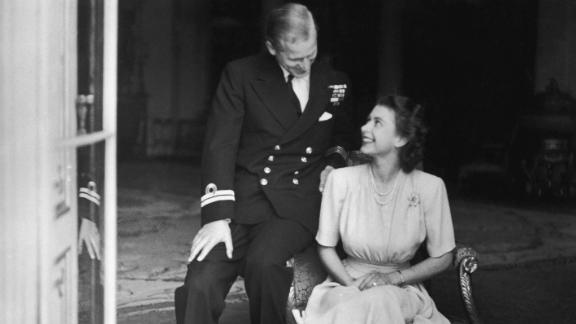 Prince Philip sits with his fiancee, Princess Elizabeth, in July 1947. He had become a naturalized British citizen and a commoner, using the surname Mountbatten, an English translation of his mother