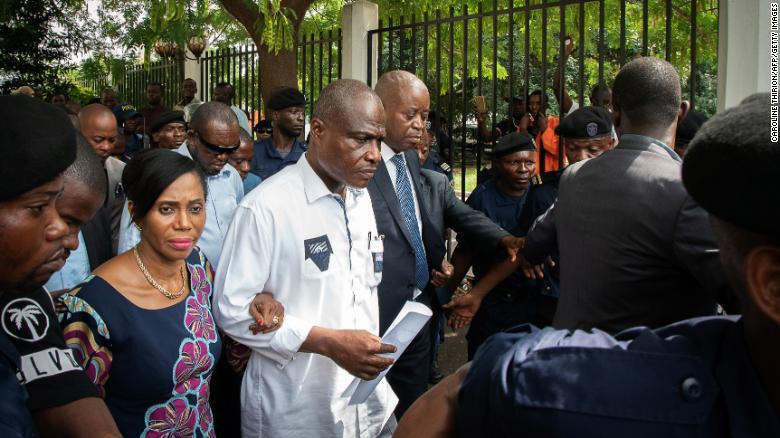 Martin Fayulu, center, leaves court Saturday in Kinshasa with his wife, Esther, after filing an appeal.
