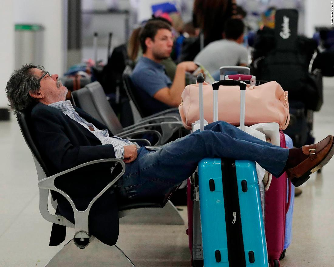 A traveler sleeps near a closed terminal at Miami International Airport on January 12.