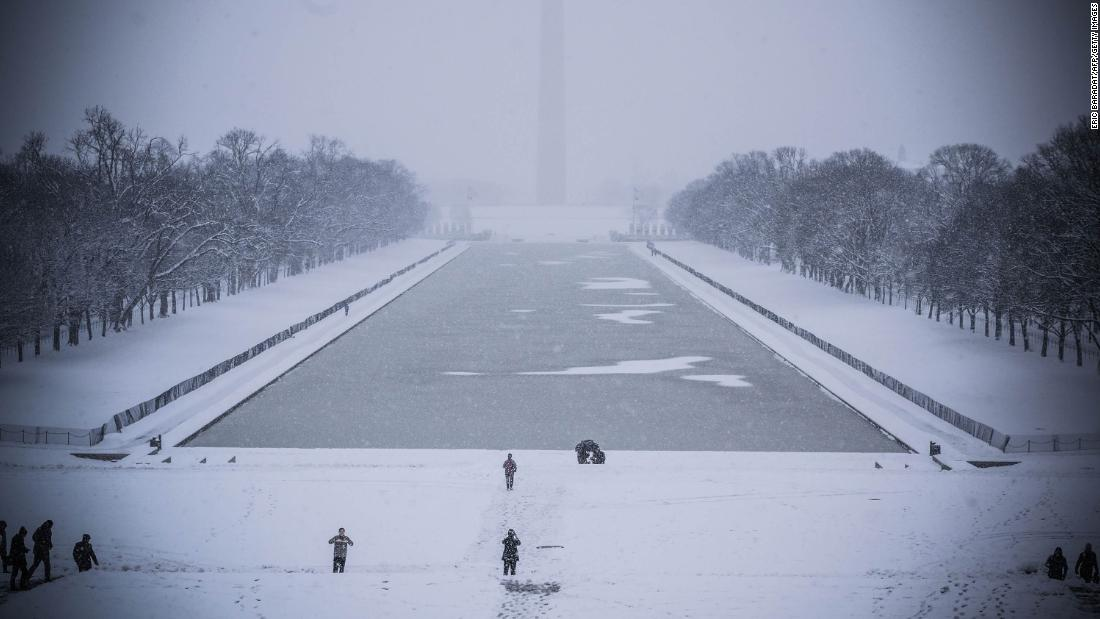 Tourists walk by the Lincoln Memorial reflecting pool as snow covers the ground.