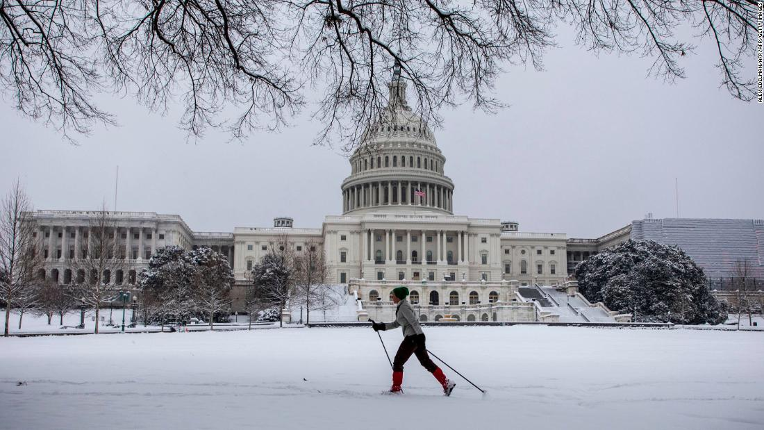 A woman skis in front of the US Capitol.