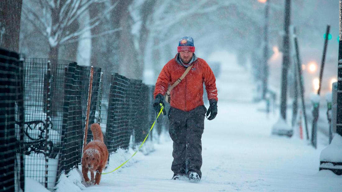 A man walks his dog as snow continues to fall in Washington.