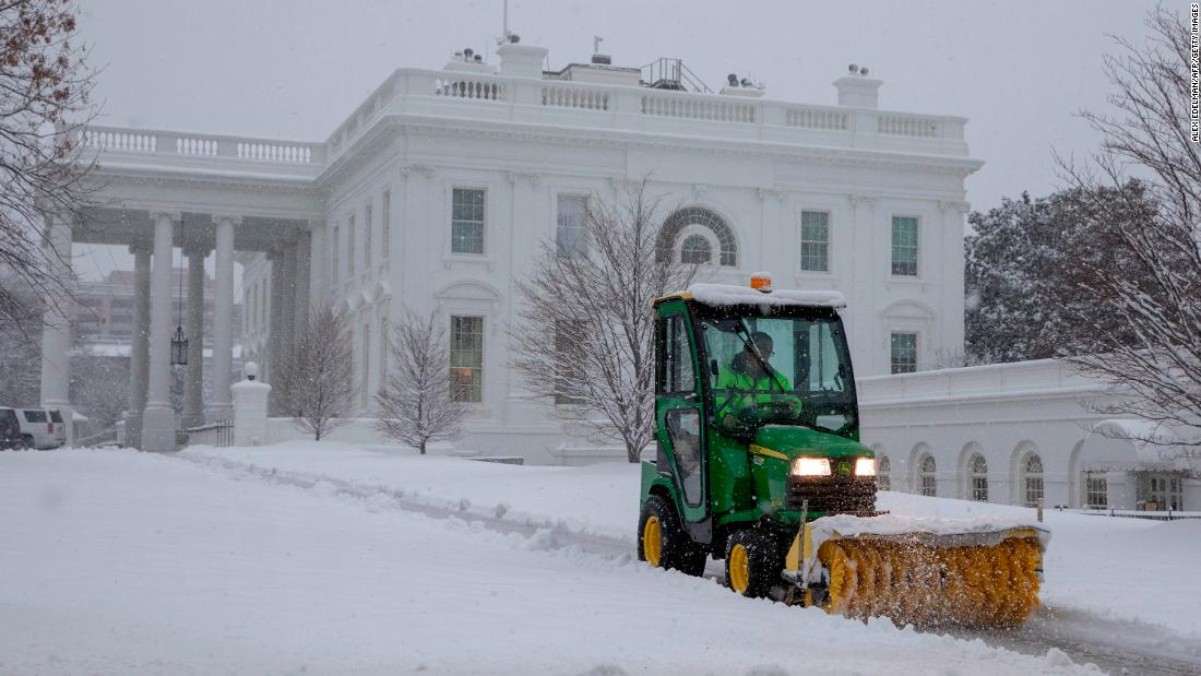 US National Park Service workers clear snow outside the White House.