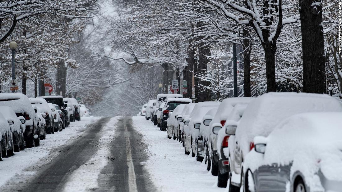 Snow covers parked cars during the winter storm in Washington.