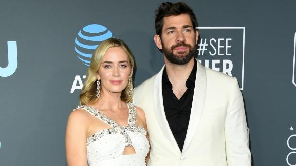 Emily Blunt wore a Prada gown, while husband John Krasinski opted for a white jacket over a black shirt.