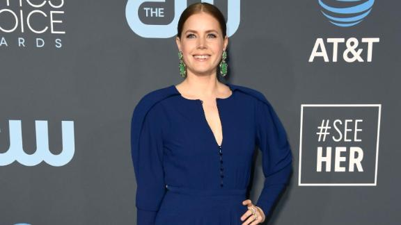 Amy Adams paired a blue long-sleeved dress with emerald green statement earnings.