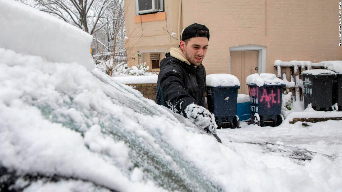 A man brushes snow off his windshield in the Dupont Circle neighborhood of Washington, DC, on January 13, 2019.