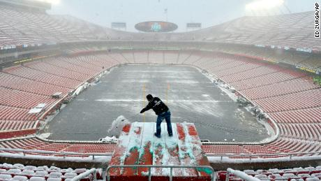 Kyle Haraugh of NFL Films clears snow from a camera location at Arrowhead Stadium on Sunday, January 13, 2019, in Kansas City, Missouri.