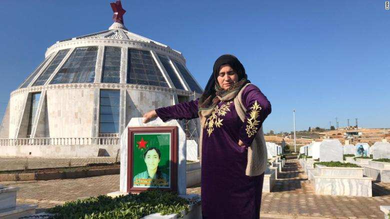 The mother of Peyman Tolhildan, 19, grieves by her grave in Kobani, northern Syria