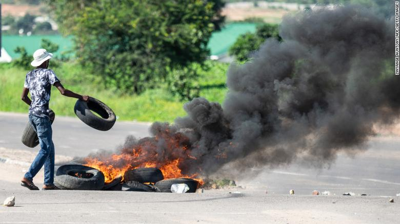 "A protesters burns tyres on a road during a ""stay-away"" demonstration against the doubling of fuel prices on January 14, 2019 in Emakhandeni township, Bulawayo."