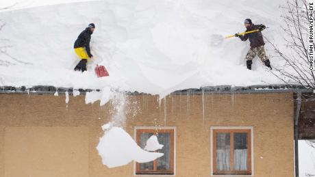 Two men try to remove snow from a roof of a house in Filzmoos, Austria.