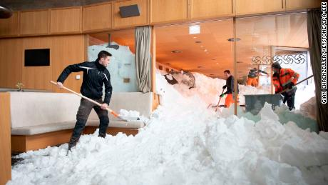 Emergency service workers clear snow from the inside a hotel on the Schwaegalp, Switzerland, after an avalanche.