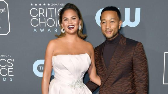 Chrissy Teigen and John Legend attend the 24th annual Critics' Choice Awards. Teigen wore a glamorous ivory gown with a high thigh slit and Legend wore a sharp dark brown suit and turtleneck.
