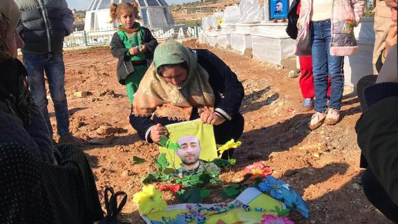 The family of 27-year-old Mahmoud Rassoul grieve by his grave in Kobani, northern Syria.