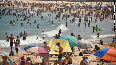Sunbathers are seen on Bondi Beach as temperatures soar in Sydney on December 28, during one of two major heatwaves to scorch the continent.