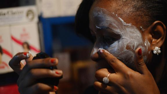 A Kenyan beautician illustrates how to apply skin-lightening cream.
