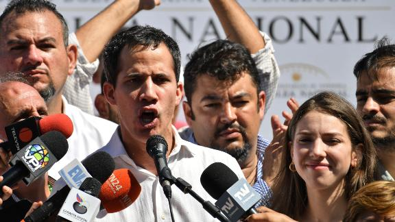 Venezuela's National Assembly president Juan Guaido, accompanied by his wife Fabiana Rosales gestures before a crowd of opposition supporters during an open meeting in Caraballeda, Vargas State, Venezuela, on January 13, 2019. - The president of the opposition-controlled but sidelined National Assembly was released less than an hour after being arrested by Venezuelan intelligence agents on Sunday, his wife said. Guaido had directly challenged the legitimacy of Nicolas Maduro as the president was sworn in for a second term on Thursday, calling for a transitional government ahead of new elections. (Photo by Yuri CORTEZ / AFP)        (Photo credit should read YURI CORTEZ/AFP/Getty Images)