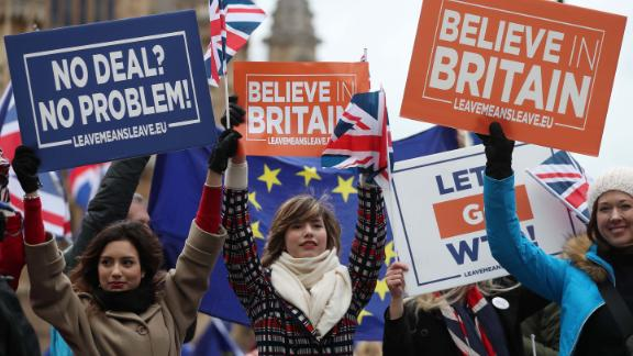 Pro-Brexit supporters hold up placards outside the UK Parliament as MPs debated.