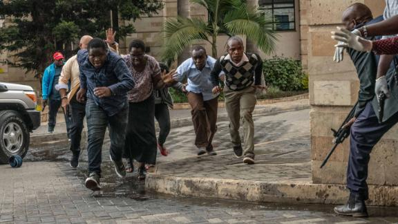 People run for cover after being rescued from the compound.