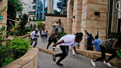 Civilians flee as security forces work to clear the buildings of a hotel complex in Nairobi during the deadly attack.