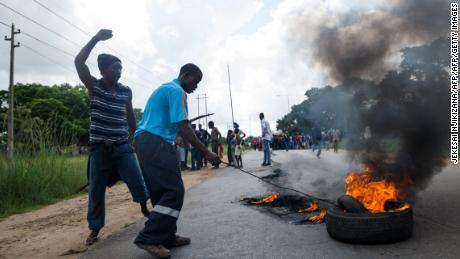 A man sets tires on fire near Zimbabwe's capital, Harare, on January 14, 2019, during protests over a large hike in fuel prices.