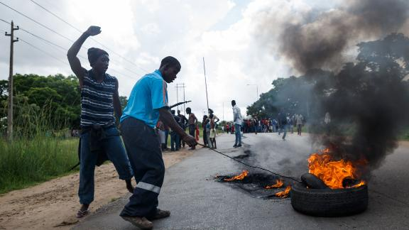 A man sets tyre on fire as angry protesters barricade the main route to Zimbabwe