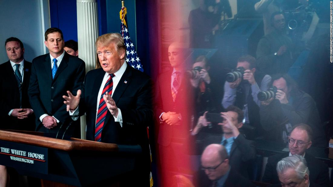"Reporters are seen reflected in an exit sign as President Trump <a href=""https://www.cnn.com/politics/live-news/first-white-house-press-briefing-2019/h_545927a35316e9fadf3ad07999ea8904"" target=""_blank"">speaks for the first time at a White House press briefing</a> on January 3. The President introduced three Border Patrol Council members who spoke about the need for a border wall."