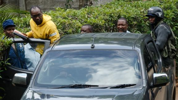 Zimbabwean cleric and activist Evan Mawarire (2nd L) enters in a police car under the supervision of policemen on January 16, 2019, after he was picked up from his home in Avondale, Harare.